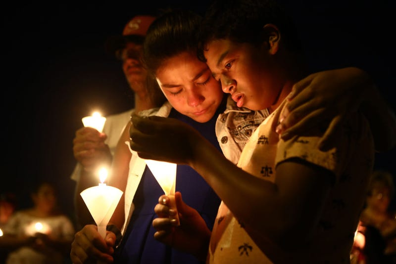 People attending a candlelight vigil in honor of the El Paso victims