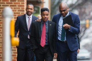 Martese Johnson (center) and his lawyer, Daniel Watkins (right), walk to the Charlottesville District Court in Virginia before Johnson's hearing March 26, 2015.Zach Gibson/Getty Images