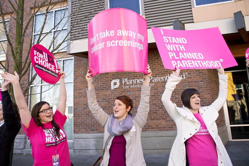 Aurora Jewell, Mandi Moshay and Kirsten Dees hold up signs following a press conference by Sen. Patty Murray (D-Wash.) outside  a Planned Parenthood Clinic on Feb. 3, 2012, in Seattle. (Stephen Brashear/Getty Images)