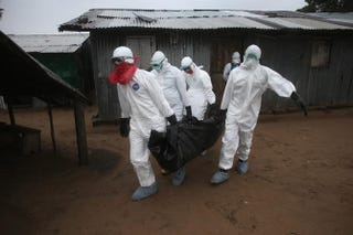 A Liberian burial team wearing protective clothing retrieves the body of a 60-year-old Ebola victim from his home near Monrovia, Liberia, on Aug. 17, 2014. The epidemic has killed more than 1,000 people in four African countries, and Liberia has had more deaths than any other country.John Moore/Getty Images