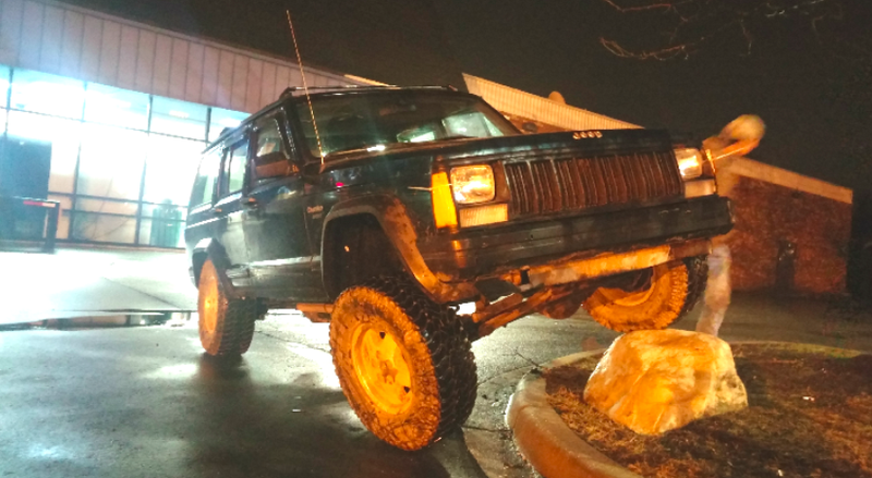 The $600 Jeep XJ flexes on a rock in a nearby strip mall.