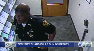 Alan Gaston standing in an office looking like a real cop in full uniform.