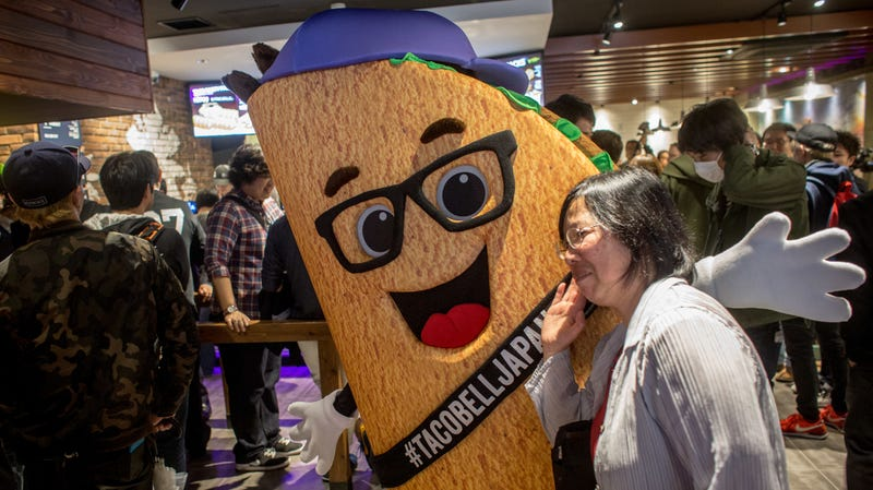 A Taco Bell mascot poses during a grand opening in 2015.