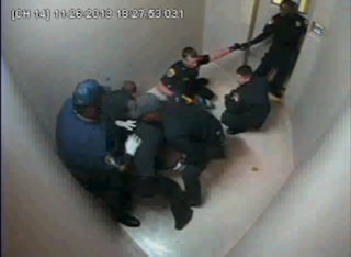 Officers surround Ervin Leon Edwards (not visible) in an attempt to restrain him.