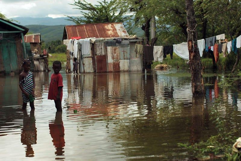 Children stand outside their flooded homes on Nov. 6, 2010, in Petite Riviere, Haiti. (Spencer Platt/Getty Images)