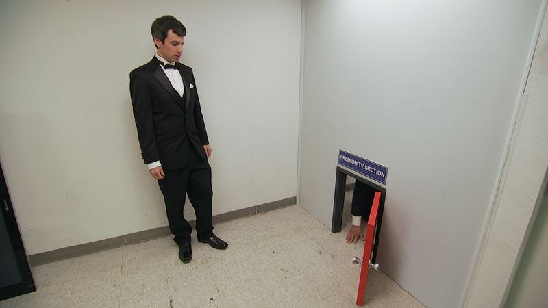 Nathan Fielder watches a customer crawl through a tiny door that supposedly leads to huge bargains. (Photo: Comedy Central)