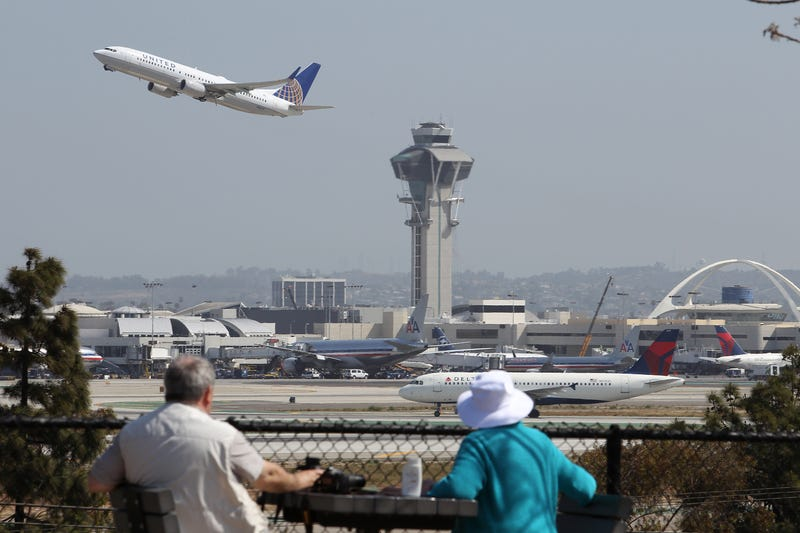 People watch as a United Airlines jet passes the air traffic control tower at Los Angeles International Airport during take-off on April 22, 2013.David McNew/Getty Images
