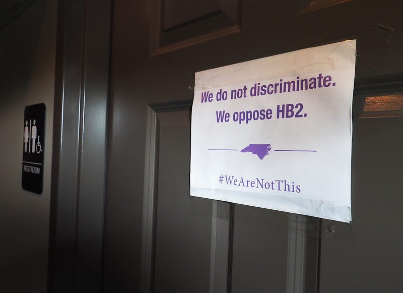 """A unisex sign and the """"We Are Not This"""" slogan are outside a bathroom at Bull McCabes Irish Pub on May 10, 2016, in Durham, N.C.Sara D. Davis/Getty Images"""