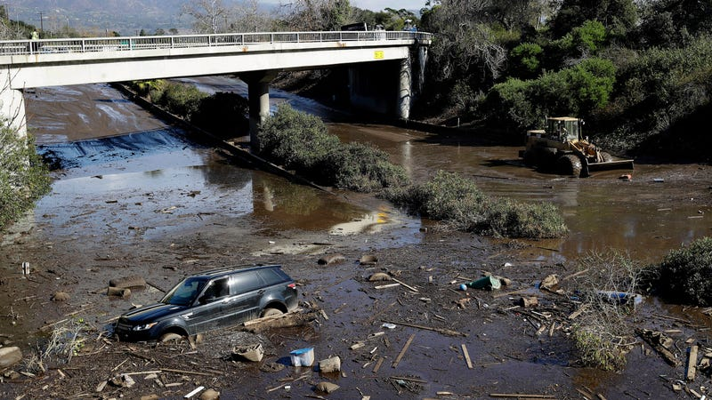 A bulldozer moves debris as a vehicle sits stranded in flooded water on U.S. Highway 101 in Montecito, CA, on January 10, 2018
