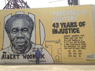 """Michel Mable stands in front of a mural of his brother, Albert Woodfox. The mural, painted by artist-activist Brandan """"Bmike"""" Odums and created in conjunction with Amnesty International USA's Art for Amnesty program, is located at 537 S. Claiborne Ave. in New Orleans.Courtesy of Angola 3 News"""