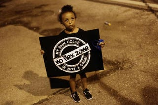 A girl in Ferguson, Mo., on Aug. 21, 2014, holds a sign as she protests the shooting of Michael Brown.Joshua LOTT/AFP/Getty Images
