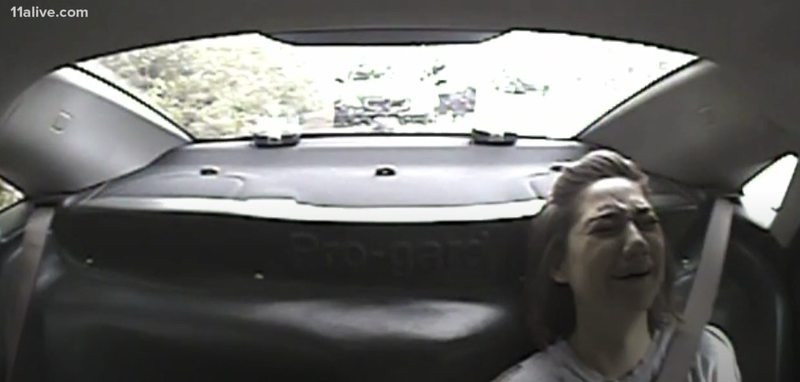 Sarah Webb seen crying in the back of a police cruiser after being arrested on the whim of a coin flip.