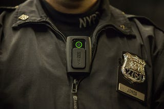 New York City Police Officer Joshua Jones demonstrates how to use and operate a body camera on Dec.  3, 2014. (Andrew Burton/Getty Images)