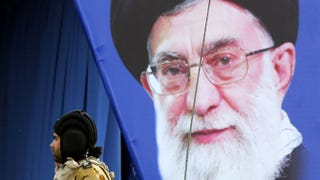 A banner bears the portrait of Iran's supreme leader, Ayatollah Ali Khamenei, as an Iranian soldier parades by during the annual Army Day military parade in Tehran, April 18, 2014.ATTA KENARE/Getty Images