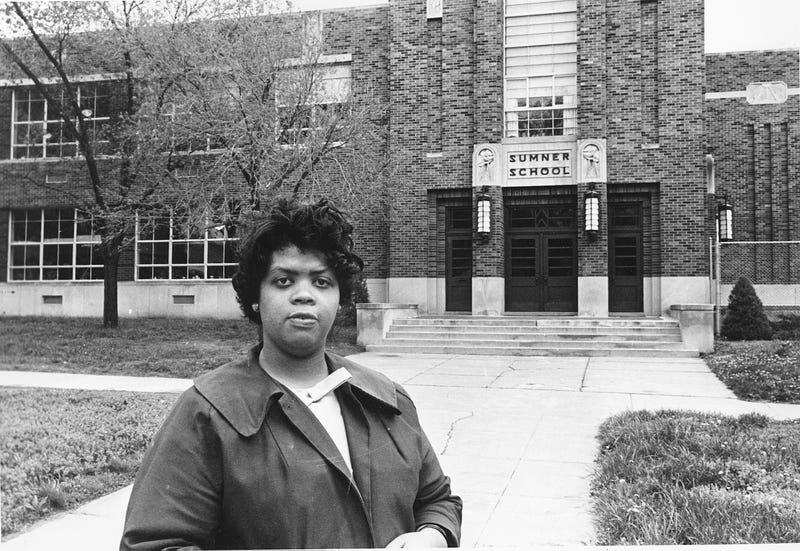 "Linda Brown Smith stands in front of the Sumner School in Topeka, Kan., on May 8, 1964. The refusal of the public school to admit Brown in 1951, then 9 years old, because she is black led to the Brown v. Board of Education of Topeka, Kansas case. In 1954 the U.S. Supreme Court overruled the ""separate but equal"" clause and mandated that schools nationwide be desegregated."