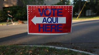 A bilingual sign stands outside a polling center at public library ahead of local elections April 28, 2013, in Austin, Texas. John Moore/Getty Images