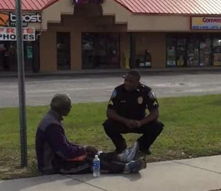 Police Cpl. Brandon Lord offers assistance to an unidentified man seated on the roadside.Philip Soukup via Facebook