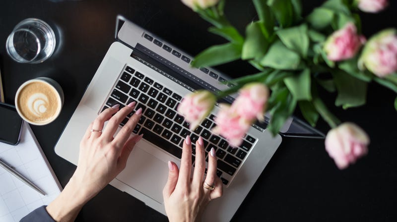 "This stock-photo ""blogger"" can afford both fresh-cut flowers and a latte."