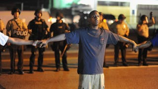 A protester joins hands with community leaders during a peaceful protest in Ferguson, Mo., Aug. 20, 2014. Michael B. Thomas/AFP/Getty Images