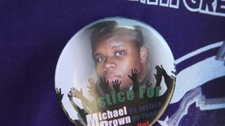 A button featuring a picture of Michael Brown is worn by a resident during a press conference with Ferguson, Mo., Police Chief Thomas Jackson Aug. 13, 2014.Scott Olson/Getty Images