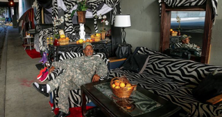 Ceola Waddell Jr., sitting in the chair of his makeshift living room under a Los Angeles freewayKTLA Screenshot