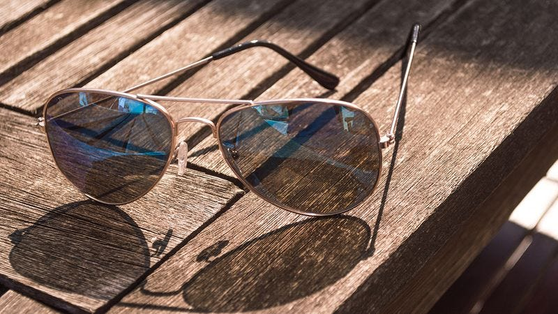 A pair of aviator sunglasses on a table.