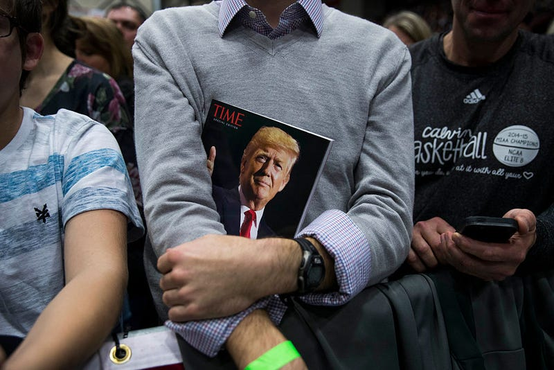 A member of the crowd holds a copy of Time magazine as President-elect Donald Trump speaks at the DeltaPlex Arena, December 9, 2016 in Grand Rapids, Michigan.