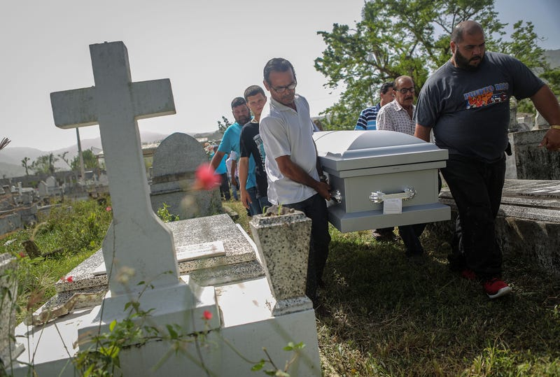 Mourners carry the casket of Wilfredo Torres Rivera, 58, who died Oct. 13, 2017, after jumping off a bridge into a lake, three weeks after Hurricane Maria, on Oct. 19, 2017, in Utuado, Puerto Rico. Rivera's family said he suffered from depression and schizophrenia and had been caring for his 92-year-old mother in a home without electricity or water in the aftermath of Maria. While the government has ruled his death a suicide, the family believes his death should be classified as a death caused by Hurricane Maria. (Mario Tama/Getty Images)