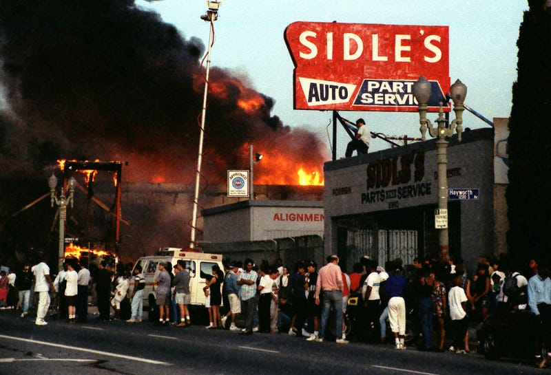 Residents in Los Angeles gather and  watch businesses burning at intersection of Pico Boulevard and Hayworth Avenue on April 30, 1992, during the riots that broke out following the not guilty verdict for policemen on trial for beating Rodney King. (Lindsay Brice/Getty Images)