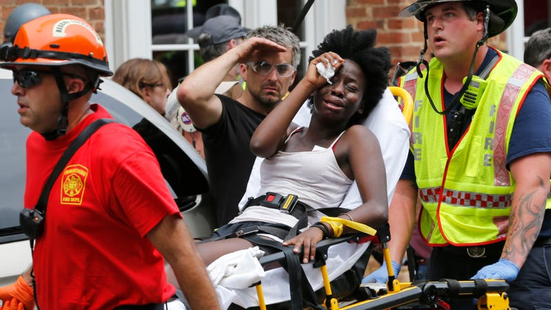 First responders help woman injured by the car attack on Saturday. Image via the AP.