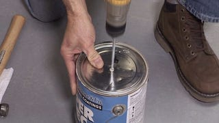 Illustration for article titled Drill a Hole Through the Paint Lid to Prevent Splashing When Mixing