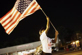 A demonstrator protesting the shooting of Michael Brown waves the American flag Aug. 21, 2014, in Ferguson, Mo.  Joshua LOTT/AFP/Getty Images