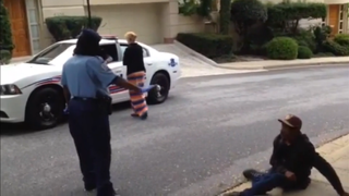 "Jody Westby (wearing long skirt) confronting police, telling them, ""Please leave our neighborhood,"" after she sees them questioning her friend, who had done nothing wrong. Youtube"