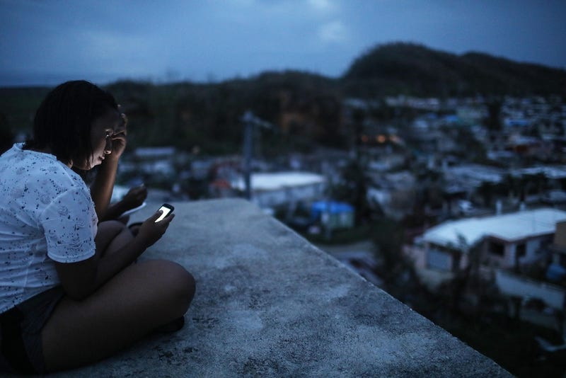 A Puerto Rican who still relies on generators for power checks her phone on her rooftop at dusk on October 5, 2017 in San Isidro, Puerto Rico. (Photo by Mario Tama/Getty Images)