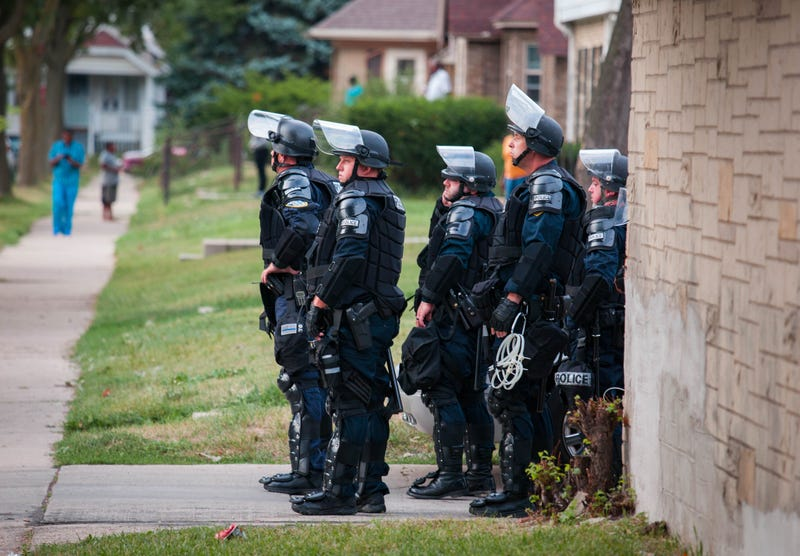 Police in riot gear wait in an alley after a second night of clashes between protesters and police in Milwaukee on Aug. 15, 2016. Hundreds of angry people have confronted police after an officer shot and killed a fleeing armed man. Darren Hauck/Getty Images