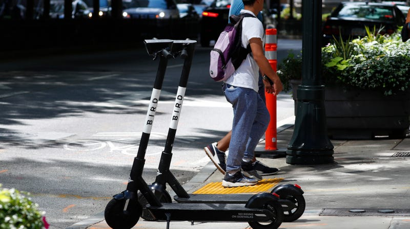 Pedestrians walk past electric scooters Thursday, Aug. 8, 2019, in Atlanta.