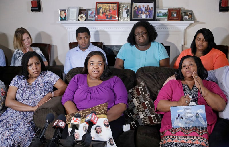 Tia Coleman, middle seated, speaks as she is surrounded by family members during a news conference at her home, Tuesday, Aug. 14, 2018, Indianapolis. Seventeen people died when the boat sank during a July 19 storm near Branson, Missouri, including 40-year-old Glenn Coleman, 9-year-old Reece, 7-year-old Evan and 1-year-old Arya. Five other Coleman relatives also died.