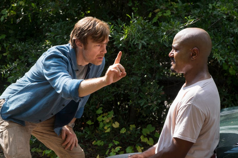 Doc Harlan (R. Keith Harris) fails to entertain Father Gabriel (Seth Gilliam).