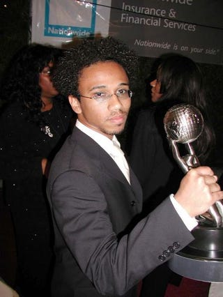 Aaron McGruder holds up his Chairman's Image Award as he attends the 33rd Annual NAACP Image Awards Feb. 23, 2002, at the Universal Amphitheatre in Universal City Plaza, Calif. Getty Images