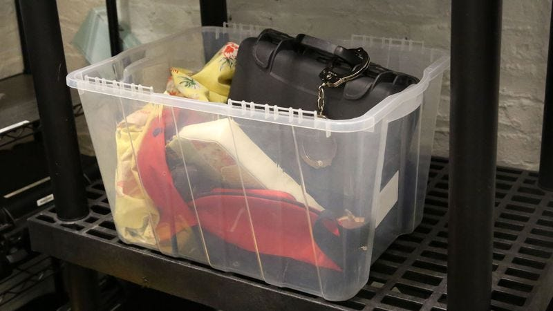 A black briefcase, along with various forgotten items, sits in a plastic bin.