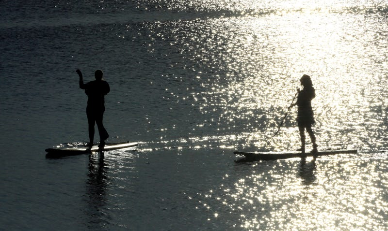 Two clothed people paddleboarding. Image via AP.