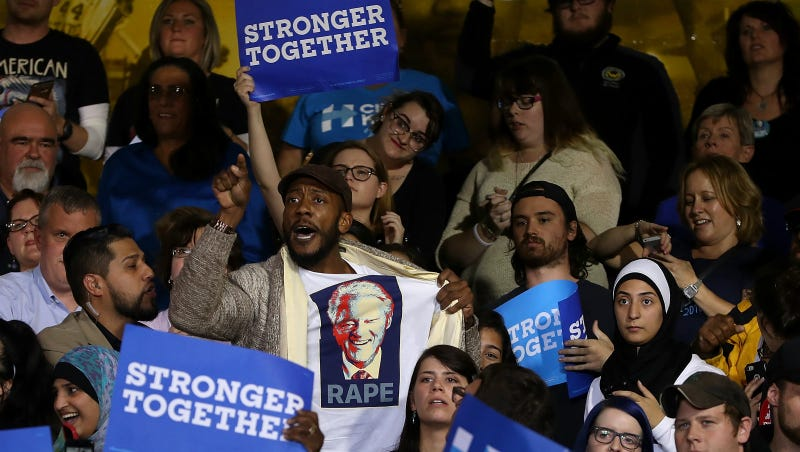 A protester wears a shirt with an image of former U.S. president Bill Clinton and the word 'rape' as democratic presidential nominee former Secretary of State Hillary Clinton speaks during a campaign rally at Wayne State University on October 10, 2016 in Detroit, Michigan. Photo via Getty