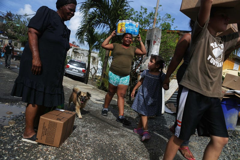 Residents carry food and water provided by FEMA  on Oct. 17, 2017, in San Isidro, Puerto Rico. (Mario Tama/Getty Images)