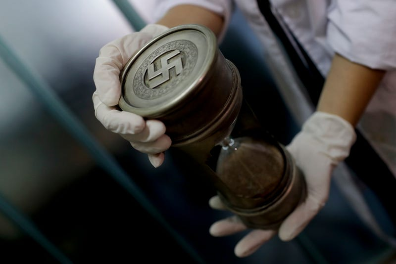 A member of the federal police holds an hourglass with Nazi markings at the Interpol headquarters in Buenos Aires, Argentina (AP Photo/Natacha Pisarenko)