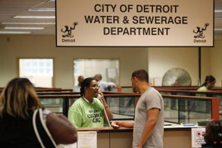 A Detroit Water and Sewerage Department worker helps a customer as she speaks on the phone during a Water Affordability Fair Aug. 2, 2014, in Detroit. Activists say black and brown Detroiters aren't getting their fair share of media attention for the work they're doing to bring the city back.JOSHUA LOTT/GETTY IMAGES
