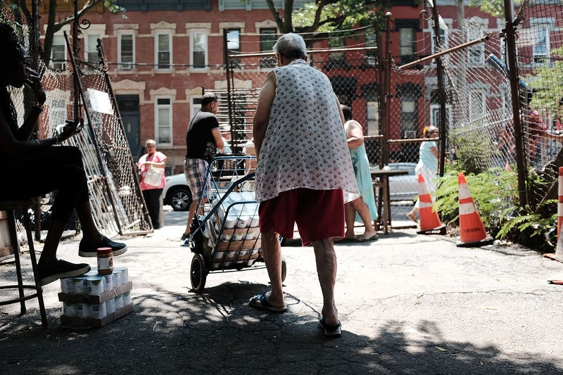 A woman walks away from a free weekly food pantry in the Bronx on July 11, 2018, in New York City