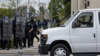 A police officer drives a van with a shattered window April 27, 2015, in Baltimore.BRENDAN SMIALOWSKI/AFP/Getty Images