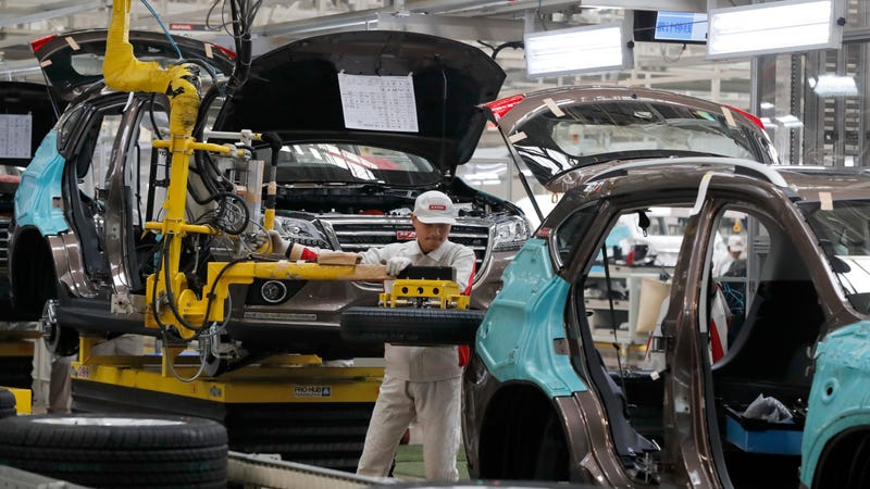 In this Feb. 19, 2017 file photo, a worker prepares to put a spare tire into a Haval SUV H2 model in the Great Wall Motors assembly plant in Baoding in north China's Hebei province. Image credit: Andy Wong/AP Images