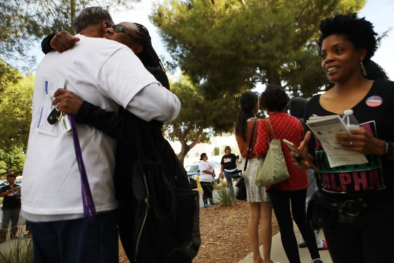 Voters hug in the line at a polling place to participate in early voting in California's 25th Congressional district on November 4, 2018 in Lancaster, California.