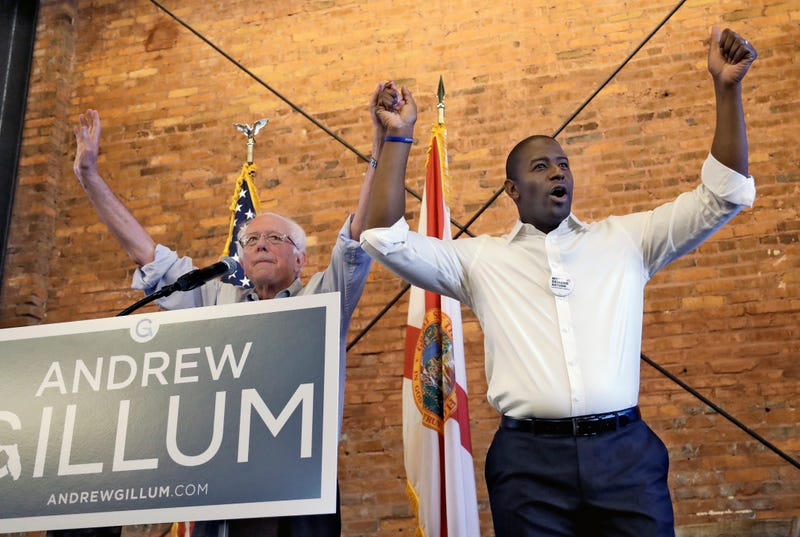 U.S. Sen. Bernie Sanders, I-Vt, left, and Democratic gubernatorial hopeful Andrew Gillum hold hands during a campaign rally Friday, Aug. 17, 2018, in Tampa, Fla.